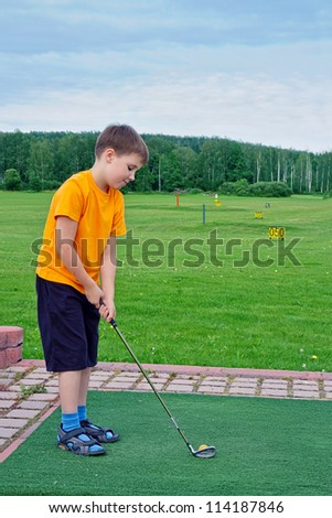 Young boy playing golf in the summer - stock photo
