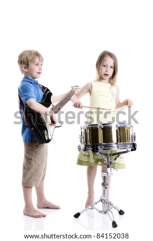 Young boy playing guitar and young girl playing drums - stock photo