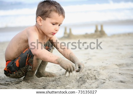 young boy playing in the sand and waves on the beach - stock photo
