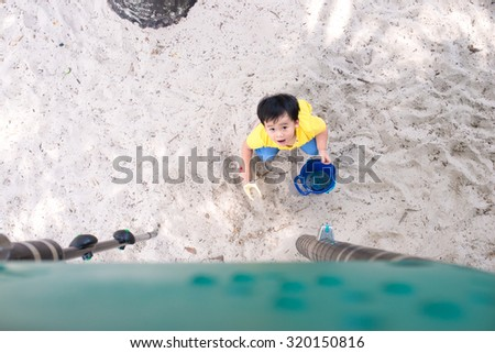 Young boy playing in the sandbox. View from above. Portrait of happy kid at playground - stock photo