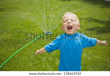 Young boy playing in the sprinklers outdoors - stock photo