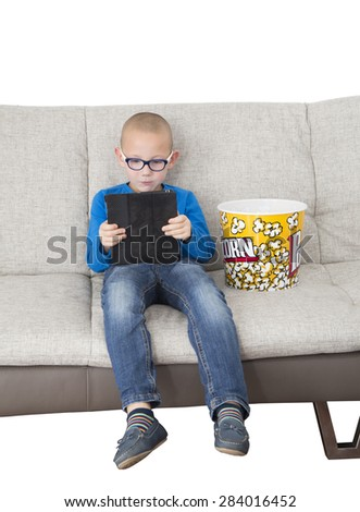 Young boy playing on a digital tablet with popcorn while sitting on the sofa - stock photo