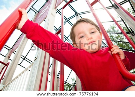Young boy playing on playground during spring. - stock photo
