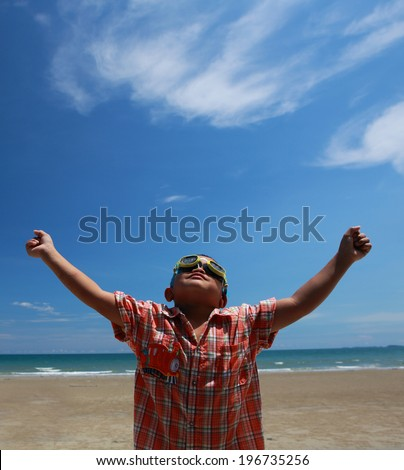 Young Boy playing on the beach with beautiful blue sky and white cloud,Happy kid with blue sky and white cloud - stock photo
