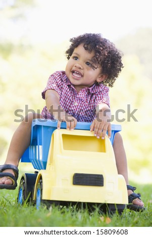 Young boy playing on toy dump truck outdoors - stock photo