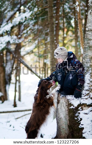 young boy playing out in the snow with his pet dog - stock photo