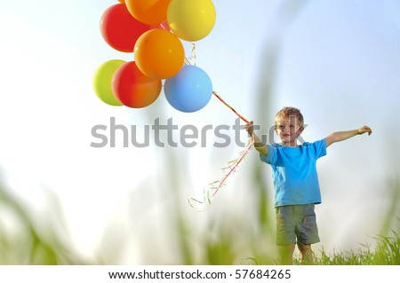 Young boy playing with a bunch of balloons outside, shot through grass in the field - stock photo