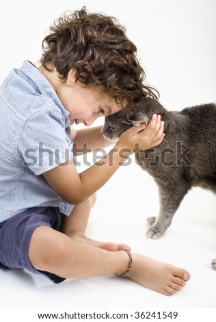 young boy playing with a gray cat - stock photo