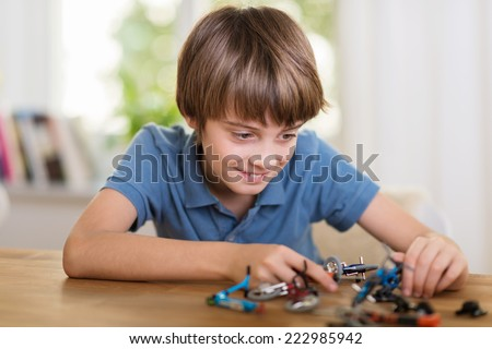 Young boy playing with a toy helicopter at home smiling a he constructs the model in an educational fun concept - stock photo