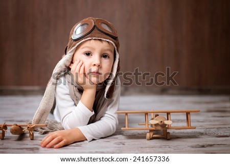 Young boy, playing with airplanes, indoors. - stock photo