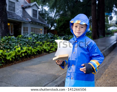 Young boy playing with toy boat in the rain wearing rain slickers and galoshes.