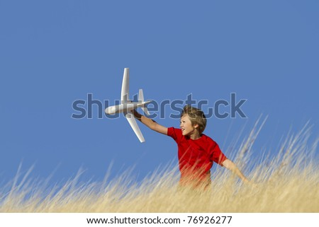 Young Boy Playing with Toy Glider Airplane in Field - stock photo