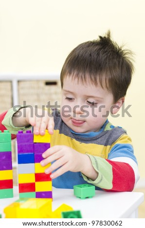 Young boy plays with connecting bricks - stock photo