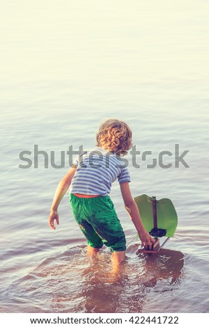 Young boy plays with his homemade sailing boat in calm lake water. It is summertime. Digital filters used for artisitc effect. He pushes the boat away from the camera into the fog like distance. - stock photo