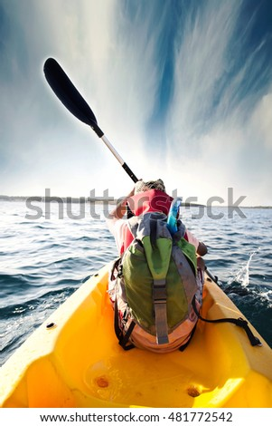 young boy plows through the waters of the sea with his canoe