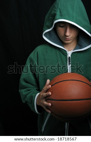 Young boy portrait holding a basketball - focus on foreground - stock photo