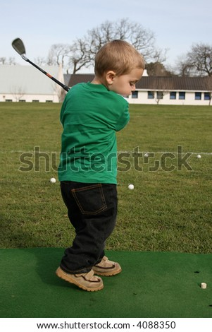 Young boy practicing his golf on the driving range - stock photo