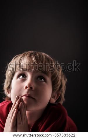Young boy praying, low key lighting. - stock photo
