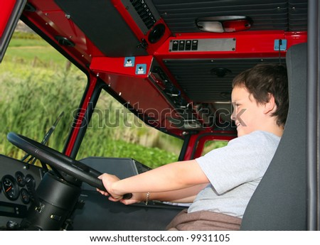 Young boy pretending to drive a fire truck - stock photo