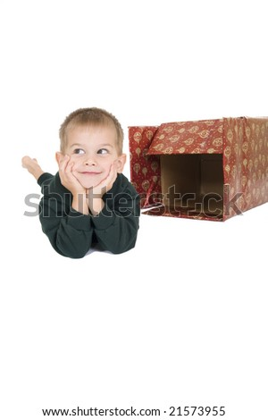 Young boy propping his head up with his hands next to a empty Christmas box. Isolated on white. - stock photo