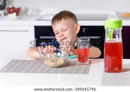 Young Boy Pushing Bowl of Breakfast Oatmeal Cereal Away in Protest While Sitting at Kitchen Table with Glass of Red Juice - stock photo