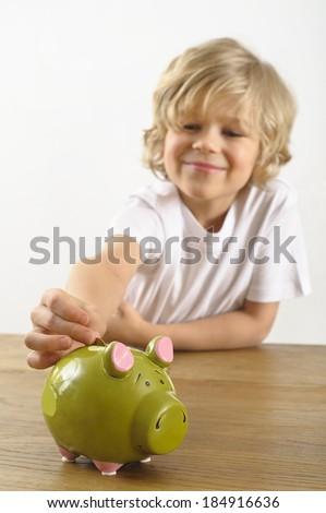 young boy puts a coin into his piggy bank - stock photo