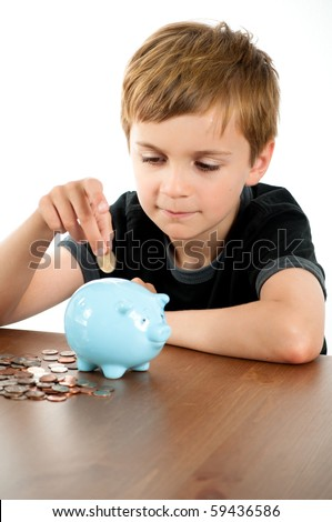 Young Boy Putting Money in Blue Piggy Bank - stock photo