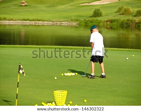 Young boy putting on the green of a golf course. - stock photo