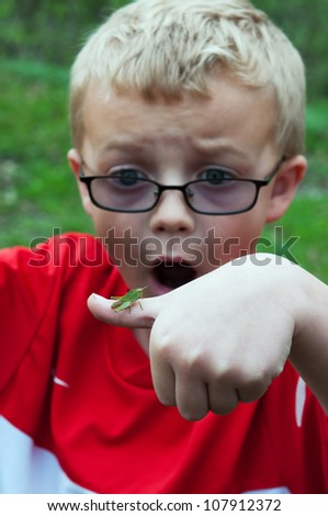 Young Boy Reacts to Insect on Finger - stock photo