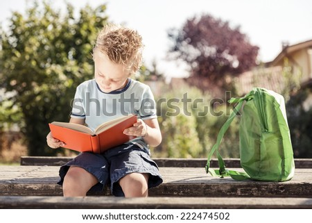 Young boy reading a book in a park. Back to school. - stock photo