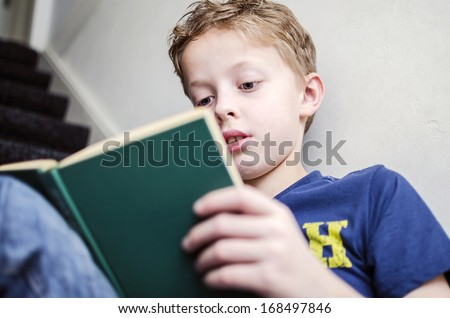 Young boy reading a book on the stairs - stock photo