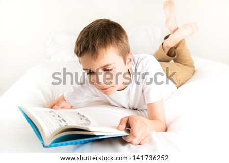 Young Boy Reading Blue Book in Bed - stock photo
