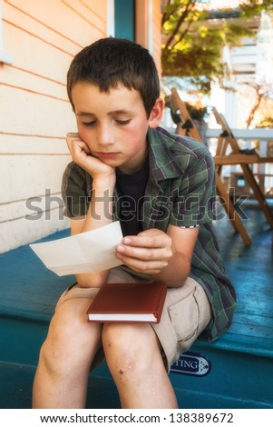young boy reading letter on steps
