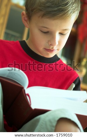 Young boy reading old, heavy book - stock photo