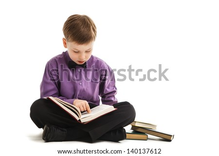 Young boy reads a book isolated - stock photo