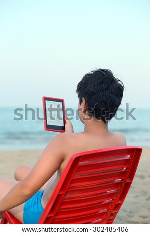 young boy reads the ebook on the sea shore in summer - stock photo