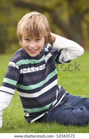 Young Boy Relaxing Outdoors Sitting On Grass - stock photo