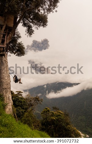 Young Boy Riding The Wildest Swing In The World Hanging From Casa Del Arbol, The Tree House Above The Abyss, Tungurahua Volcano Explosion On March 2016 In The Background, Ecuador, South America  - stock photo