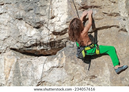Young boy rock climber in search of for his next grip - stock photo