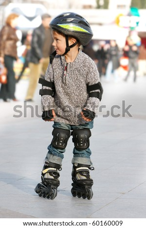 young boy rollerskating in city