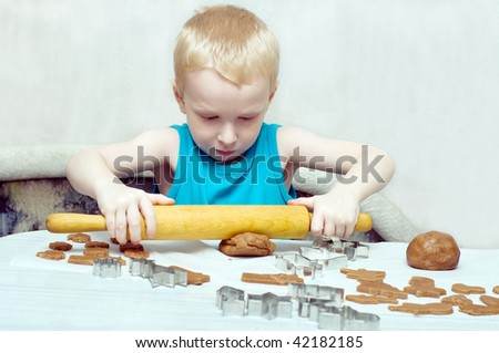 young boy rolling gingerbread dough for christmas cookies - stock photo