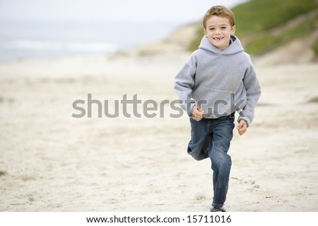 Young boy running on beach smiling - stock photo