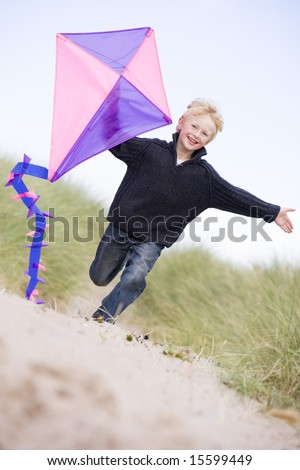 Young boy running on beach with kite smiling - stock photo