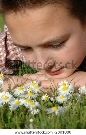 Young boy's face closeup in a daisy field - stock photo