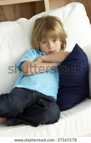 Young Boy Sat on Sofa at Home - stock photo