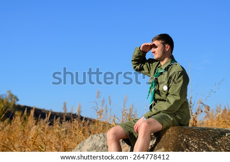 Young Boy Scout in Uniform Watching Over the Brown Field on A Sunny Day While Sitting on the Boulder. - stock photo