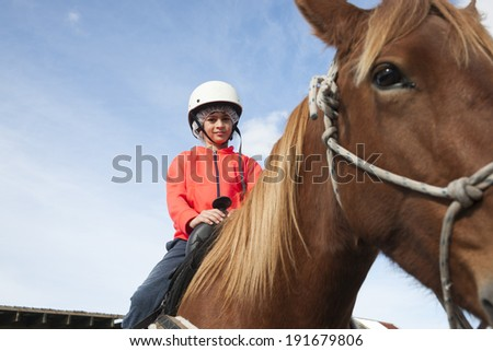 Young boy seated on horseback, learning to ride. - stock photo