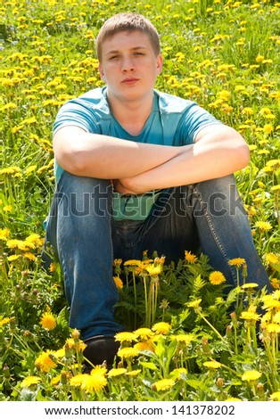 Young boy sits on dandelion field in summer - stock photo