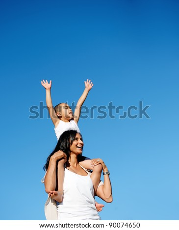 young boy sits on his moms shoulders and reaches for the sky - stock photo