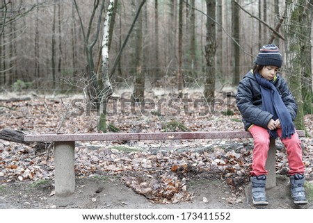 Young boy sitting alone on a rustic wooden bench looking down at the ground with a sad wistful expression through loneliness. - stock photo